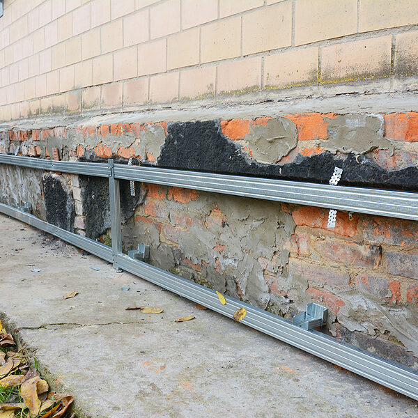 Old house foundation wall repair, renovation with installing metal sheets on metal frame for waterproofing and protect from wetness.
