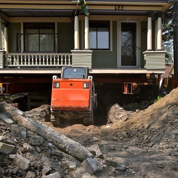 A house under foundation repair rests on strong girders as a backhoe removes concrete and dirt from underneath.