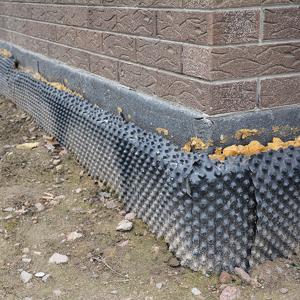 Foundation insulation with water proofing and damp proofing in problem corner area. House basement, foundation insulation details with waterproofing membrane